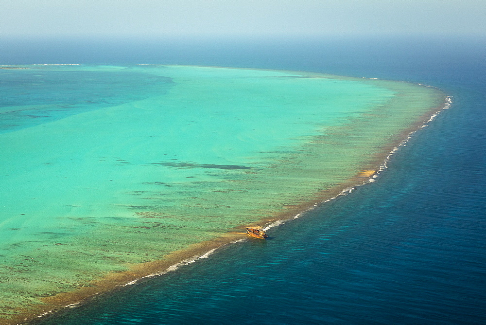 High angle view of blue ocean in Belize with ship grounded on reef