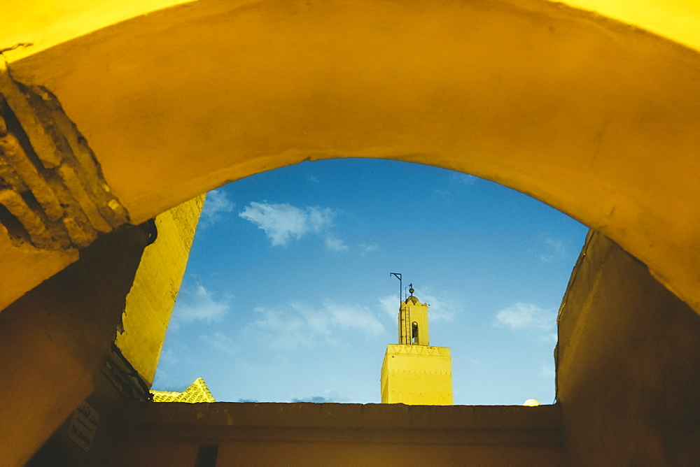 Photograph with Koutoubia Mosque minaret seen through arch, Medina, Marrakech, Morocco