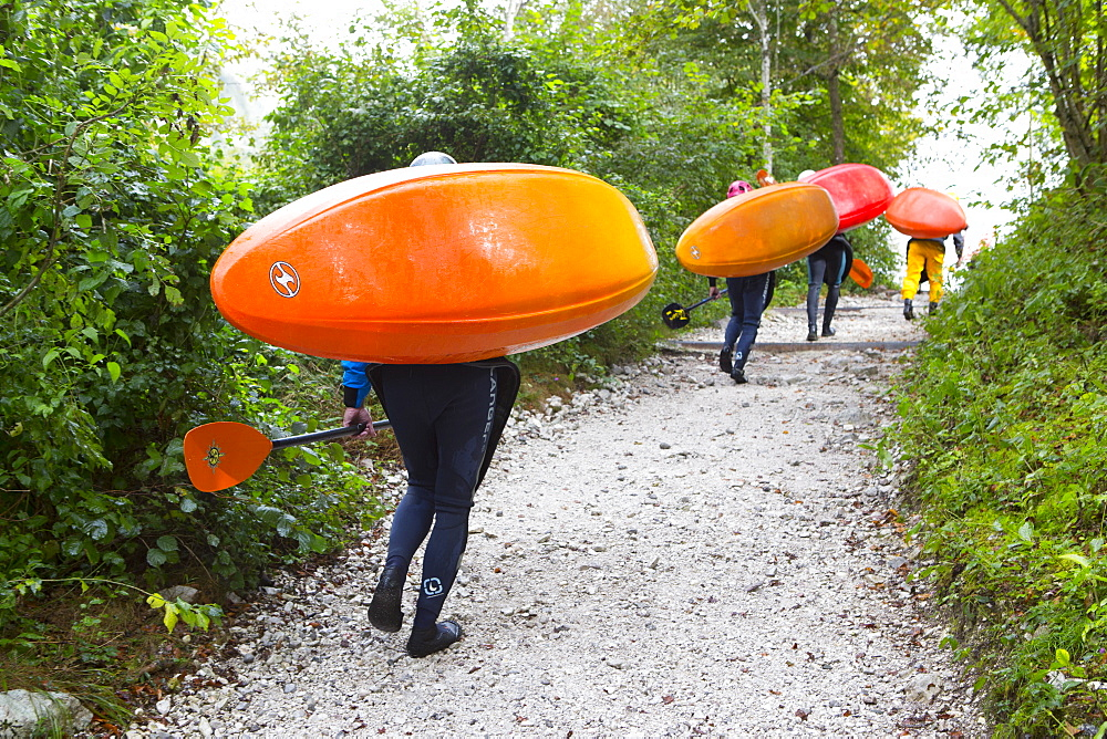 Kayakers carrying their colorful kayaks to river Soca near Bovec, Triglav, Slovenia - 857-95057