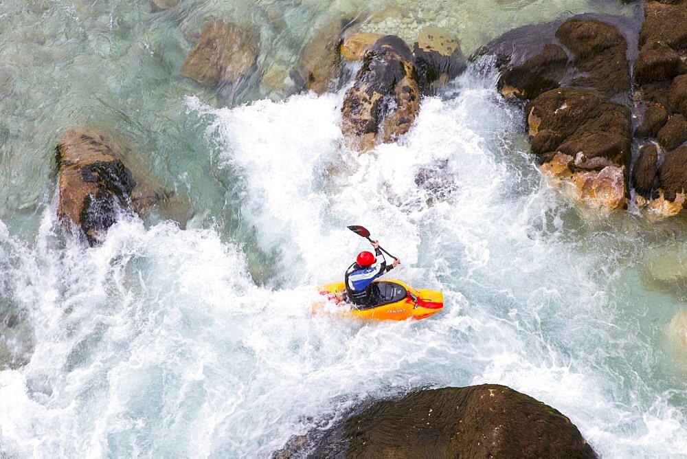 Male kayaker crossing whirlpool in green colored Soca river near Bovec, Slovenia