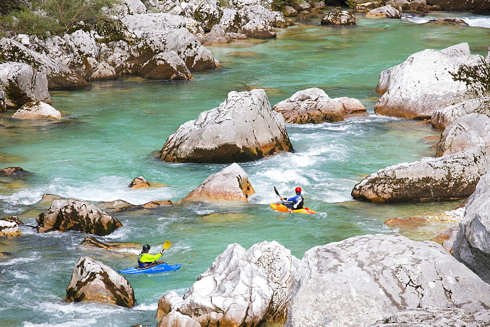 Male kayakers on green colored Soca river near Bovec, Slovenia