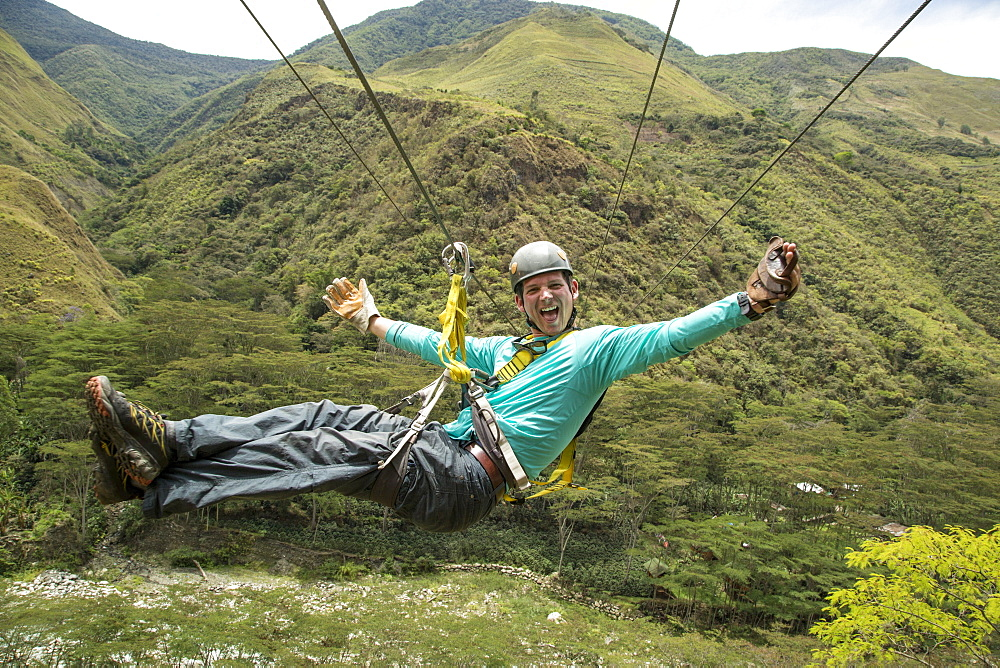 Adventurous man having fun riding on zipline through Amazon forest, Santa Teresa, Cusco region, Peru