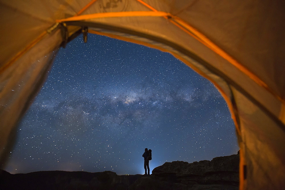 Silhouette of backpacker standing against starry night sky and Milky Way galaxy visible from inside of pitched tent, New South Wales, Australia