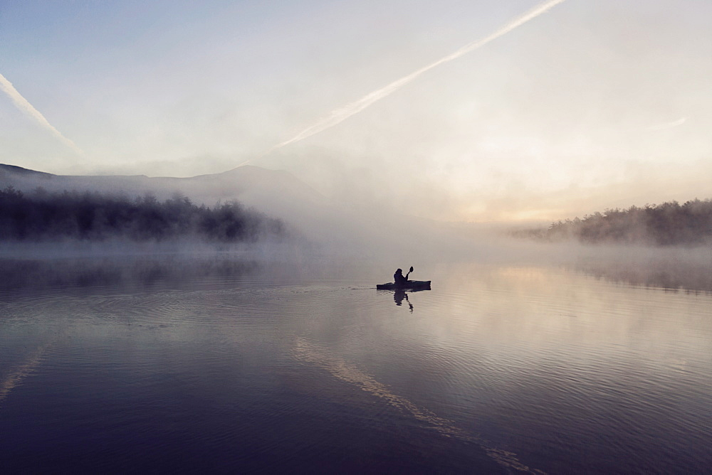 Young woman enjoys early morning paddle in kayak through mist on Daicey Pond in Maine's Baxter State Park, USA