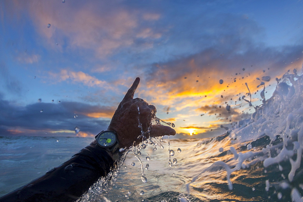 Person throwing shaka sign in surf at dawn