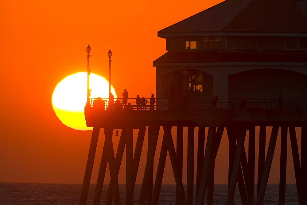 Sun setting behind pier at Huntington Beach, Orange County, California, USA