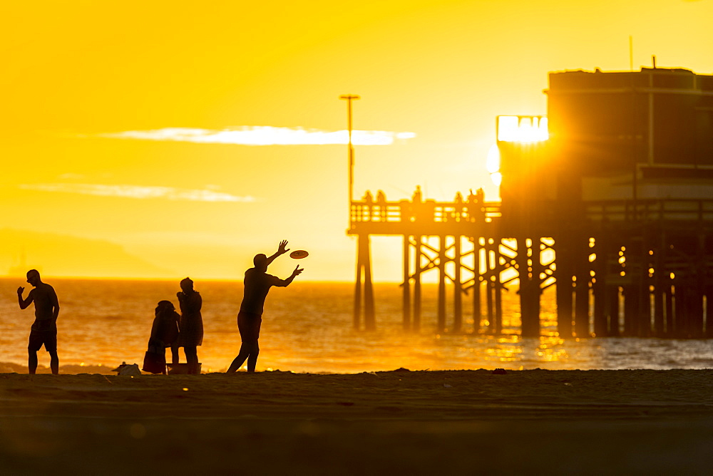 People playing plastic ring near Newport beach pier, Orange county, California, USA