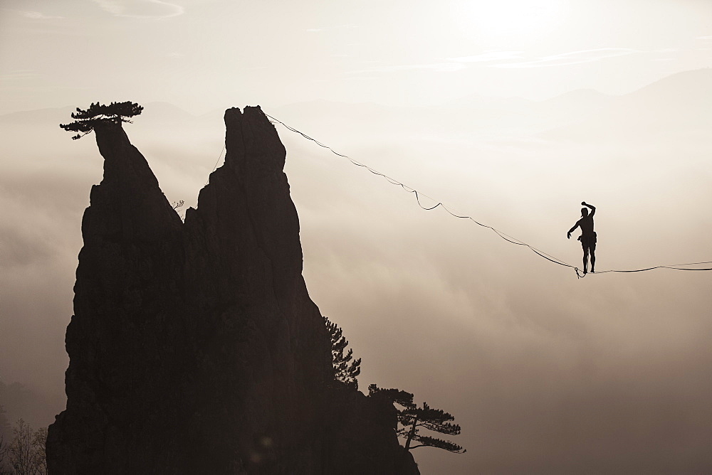 Silhouette of man balancing on highline high above foggy hills, Lower Austria, Austria