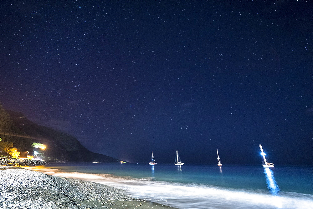 View of sailboats anchored in sea near beach at night, Black Sand Beach, Basse Terre, Guadeloupe