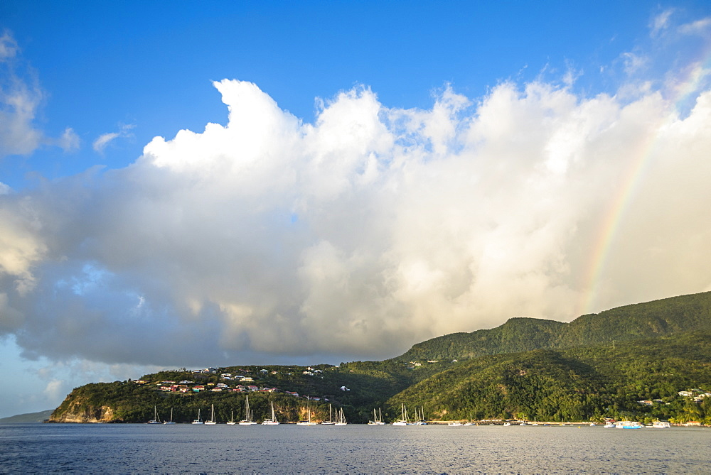 Scenic view of coastline with anchored sailboats with rainbow in background, Bouillante, Basse Terre, Guadeloupe