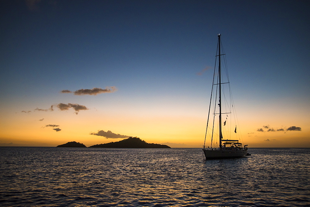 Silhouette of single sailboat in sea at sunset, Bouillante, Basse Terre, Guadeloupe
