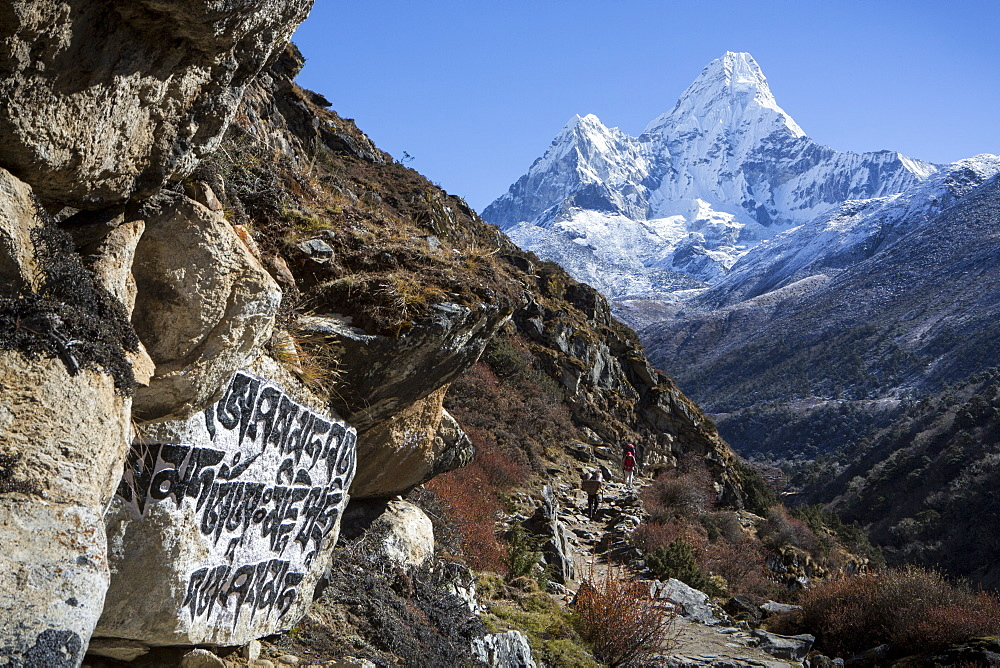 Stone carvings seen in a rock alongside the trail to Everest Base Camp, seen with the peak of Ama Dablam in the background, Khumbu, Nepal