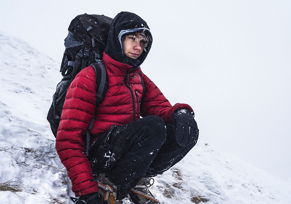 Teenage backpacker crouching while resting while trekking in winter in Tatra Mountains, Malopolskie Province, Poland
