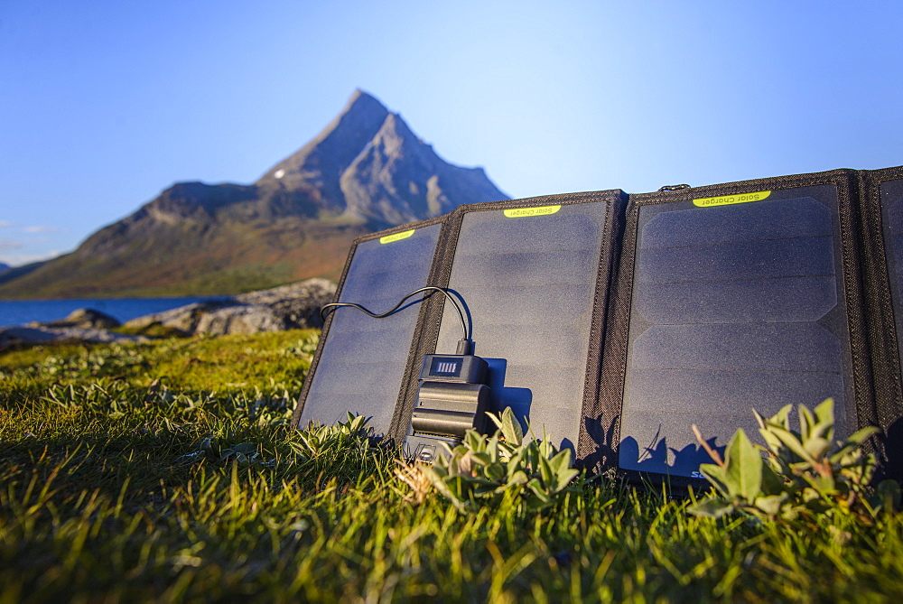 Solar charger lying in grass in front of mountain - 857-95195