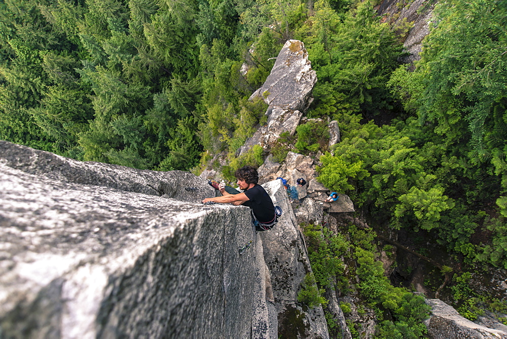 View from above of adventurous rock climber climbing challenging cliff, Squamish, British Columbia, Canada