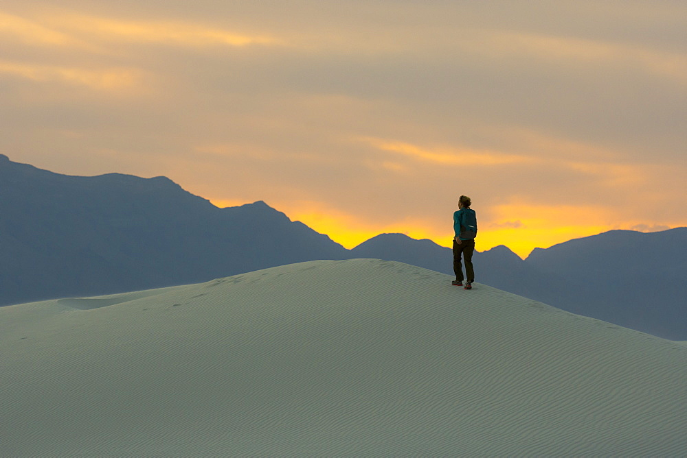 Rear view of female backpacker hiking in desert of White Sands National Monument at sunset, Alamogordo, New Mexico, USA