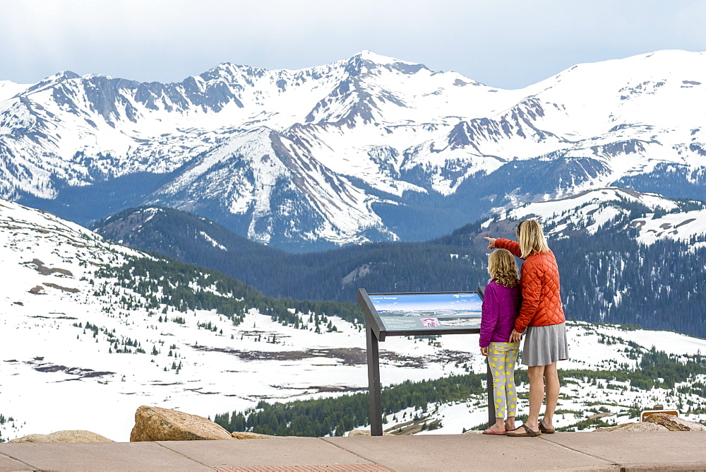 Mother and daughter standing in beautiful natural scenery with snowcapped mountains at Trailridge Road looking at Never Summer Range, Rocky Mountain National Park, Estes Park, Colorado, USA