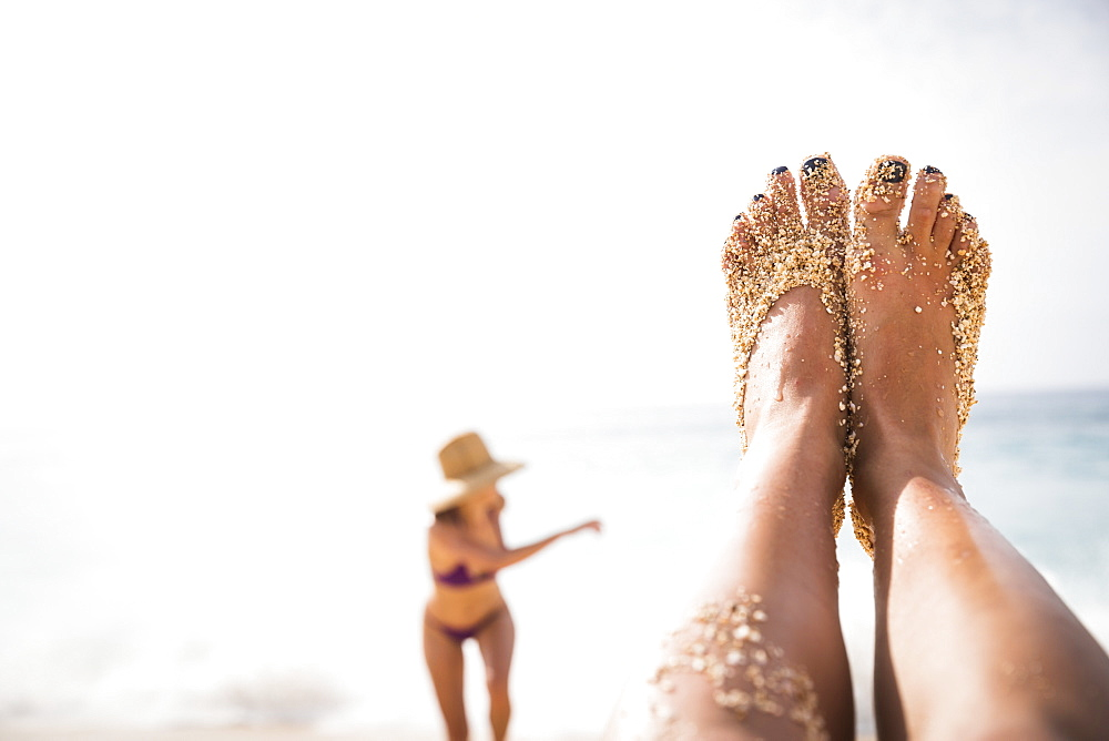 Feet of woman covered with sand on beach