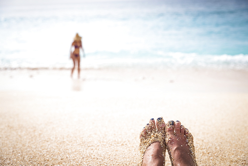 Feet of woman covered with sand on beach and woman in bikini in background