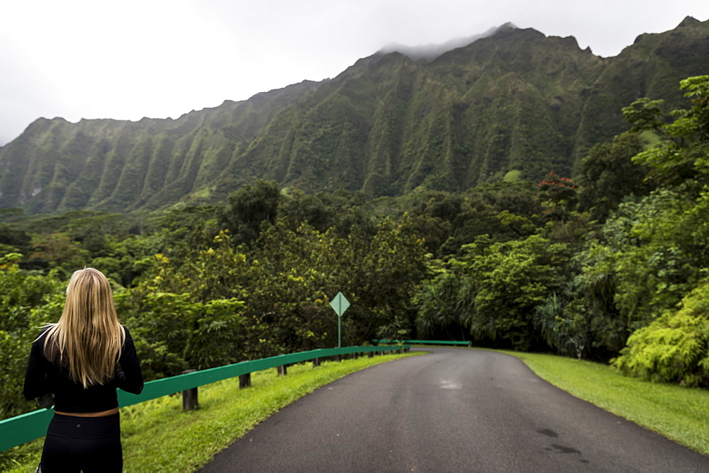 Rear view shot of blonde woman standing in scenery with road and mountains, Kaneohe, Oahu, Hawaii Islands, USA