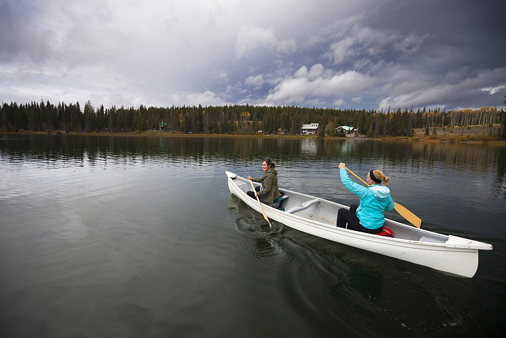 Two women canoeing on Lac Le Jeune, Kamloops, British Columbia, Canada