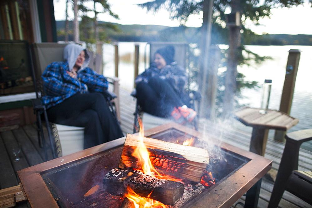 Two laughing women sitting around burning campfire