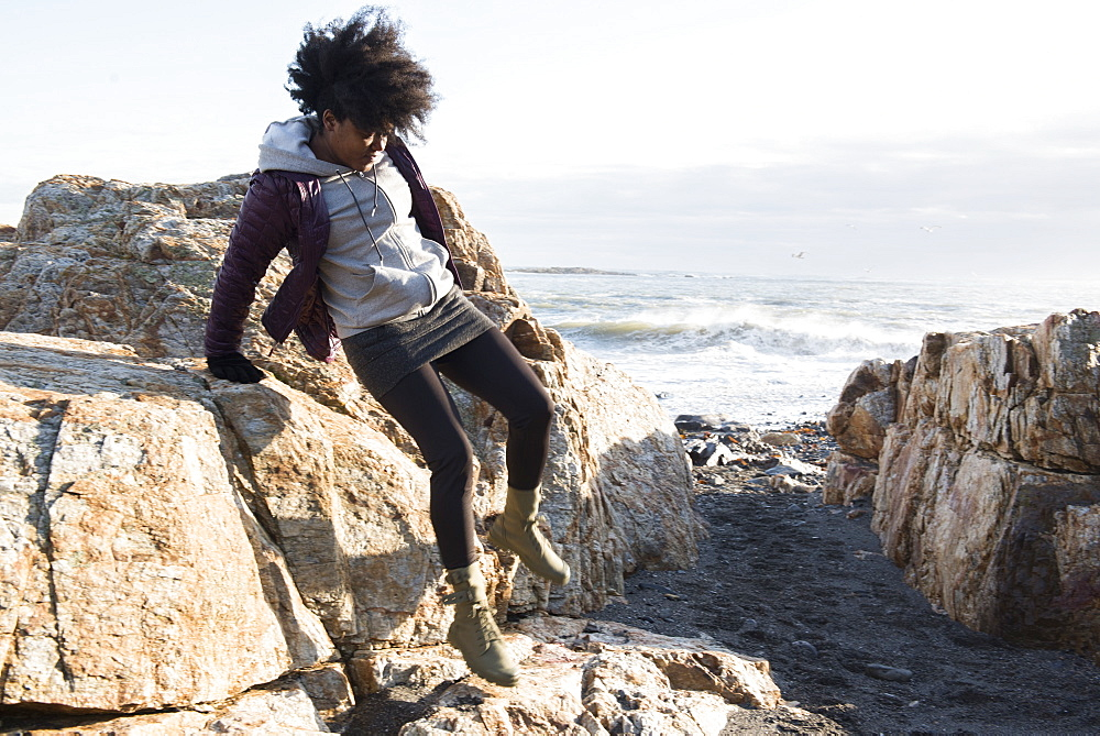 An African American woman in a purple jacket jumping down from a rock near the sea