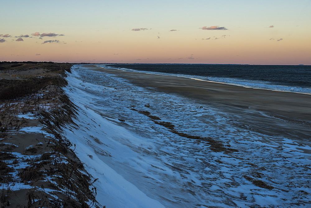 Snow covered dunes along the Atlantic Ocean at sunset on Plum Island, Parker River Wildlife Refuge, Newburyport, Massachusetts, USA