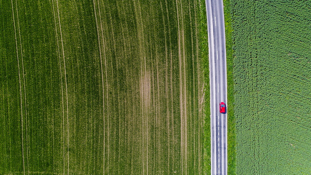 Aerial view of car driving down road surrounded by fields, Genolier, Vaud Canton, Switzerland - 857-95317