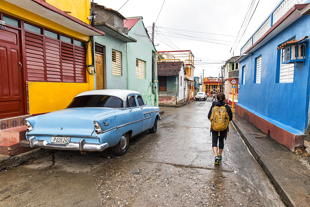 Rear view of female tourist walking on street by vintage car in Baracoa, Guantanamo Province, Cuba - 857-95328