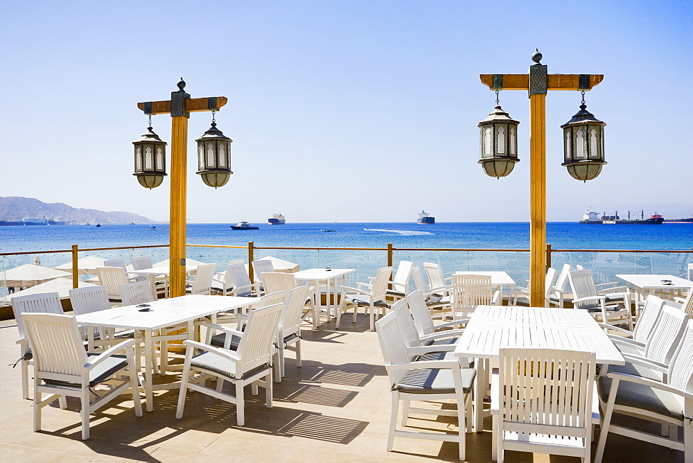 Patio with tables and chairs and Middle Eastern lamps overlooking the Gulf of Aqaba, Aqaba, Jordan
