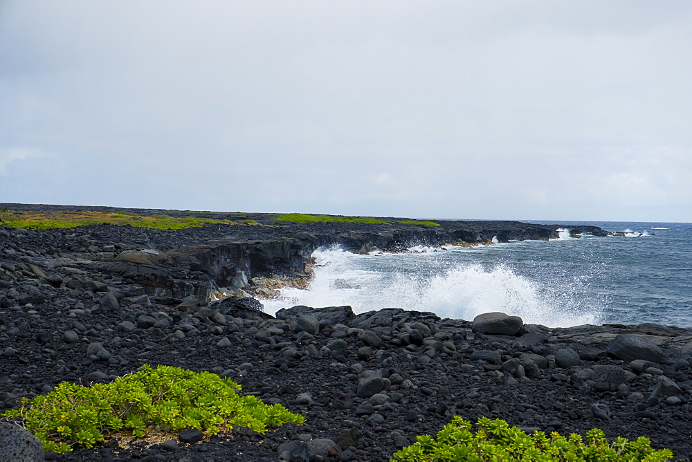 Coastal hiking scenic of the shore with waves crashing against the cliffs along the famed Puna Coast Trail to Halape Beach. The trail is 11.3 miles of rugged hiking for backpackers with no shade or water in the extreme terrain of Hawaii Volcanoes National Park, Hawaii, USA