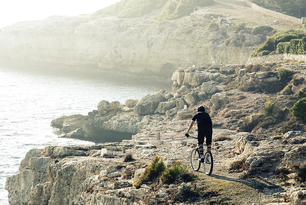 Rear view shot of adventurous mountain biker riding on coastal cliffs