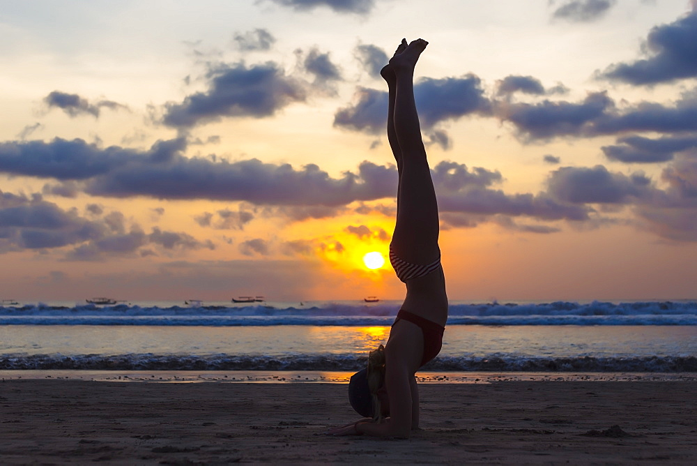 Side view of young woman doing handstand on beach at sunset