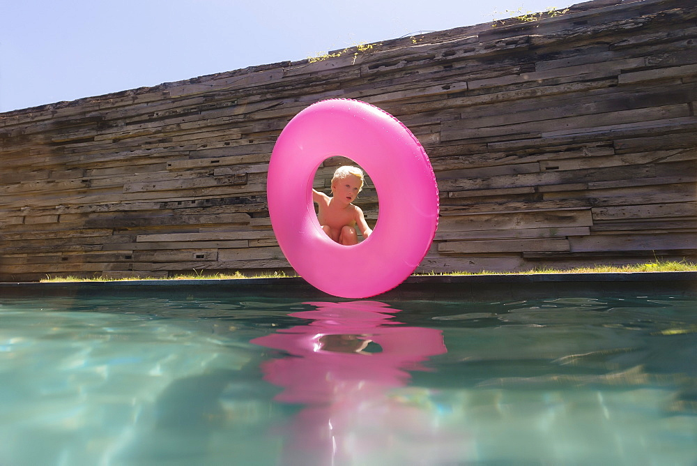 Single blonde boy with pink inflatable ring near swimming pool