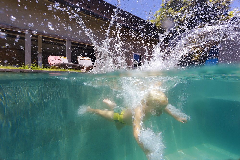 Underwater view of boy swimming in pool after diving into water