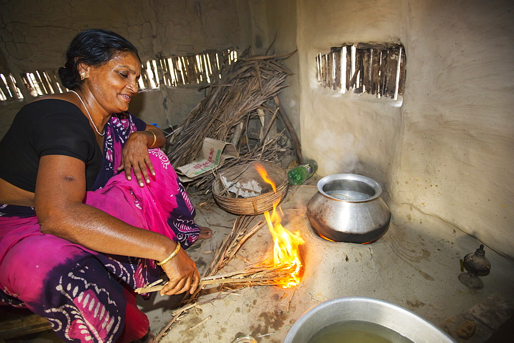 A villager woman in a remote subsistence farming village on an island in the Sundarbans, the Ganges Delta in Eastern India that is very vulnerable to sea level rise. She is cooking on a traditional clay oven, fueled by biofuel (rice stalks), low carbon cooking.