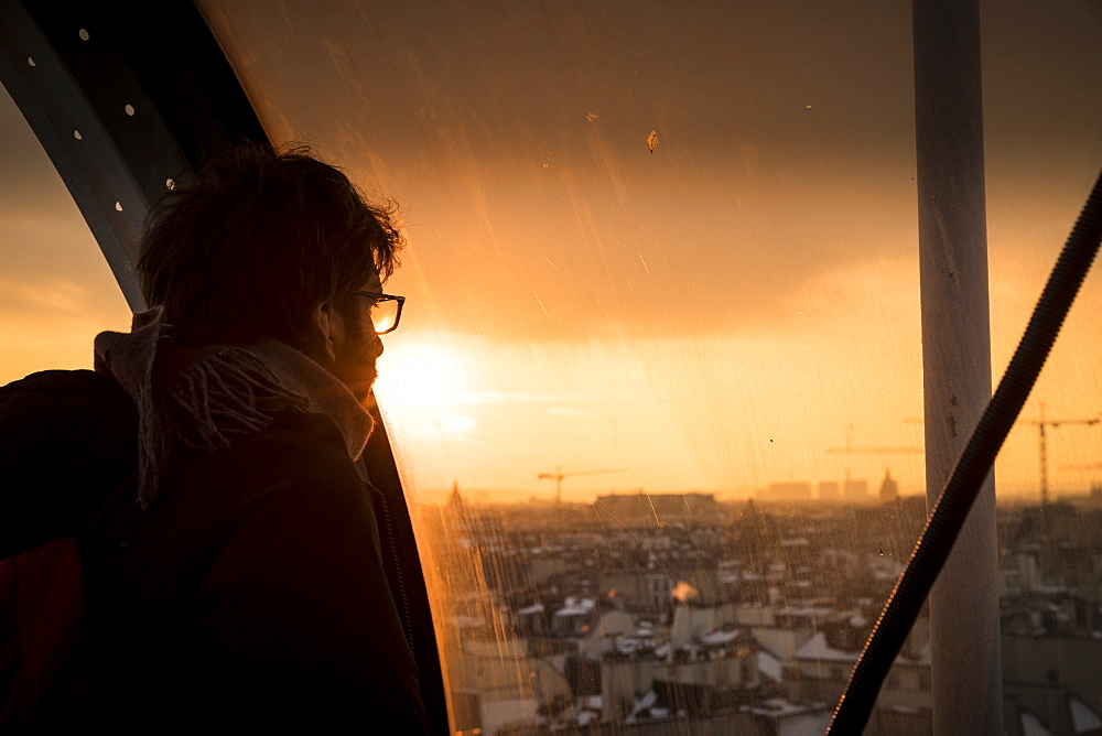Man looking through window at sunset at view of Paris, France in Centre Georges Pompidou - 857-95463