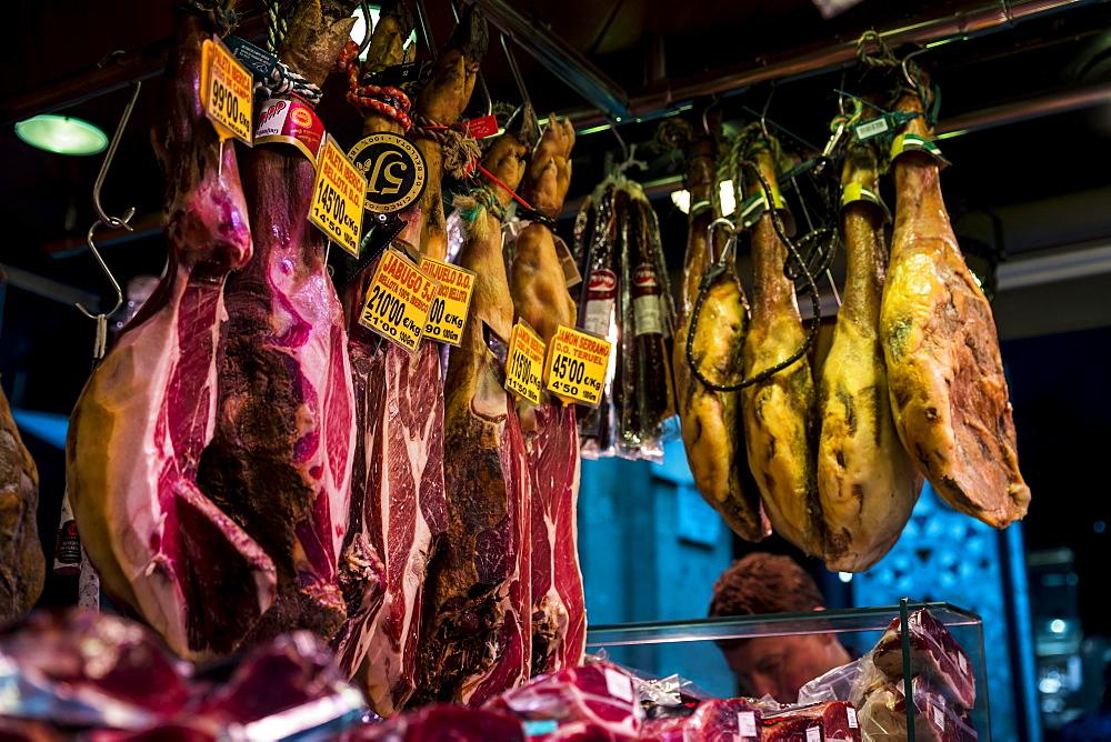 Various meat hanging in La Boqueria market in Barcelona, Spain