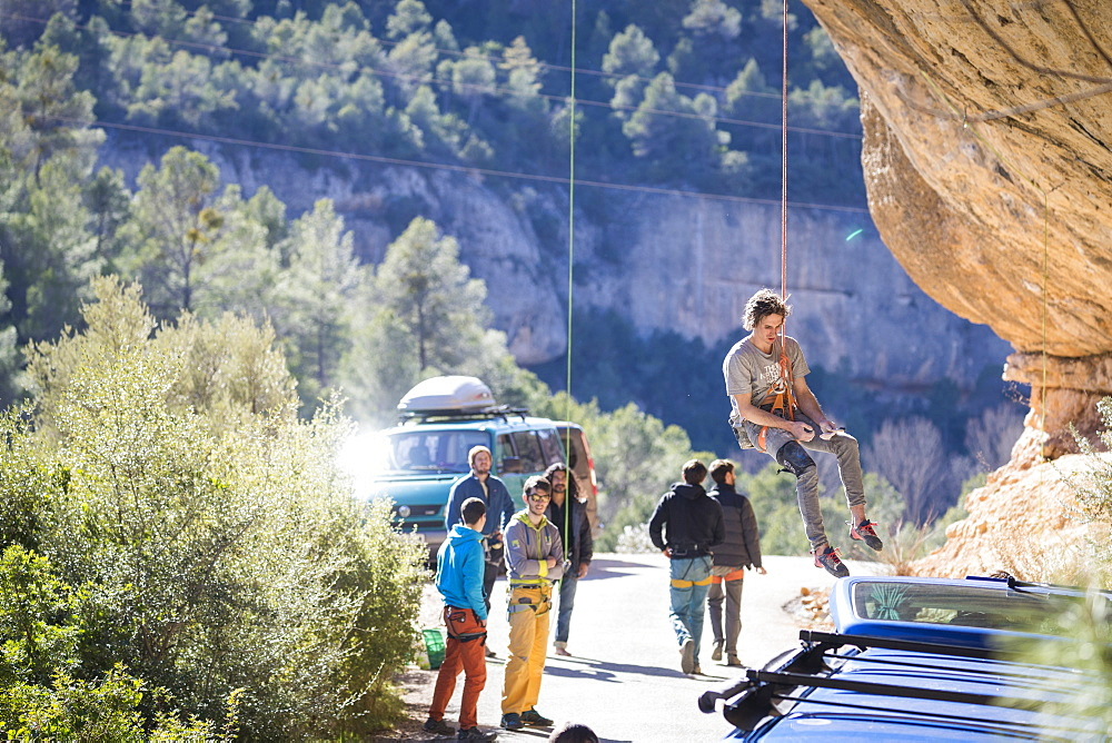 Male climber getting lowered from popular climbing crag, Margalef, Catalonia, Spain