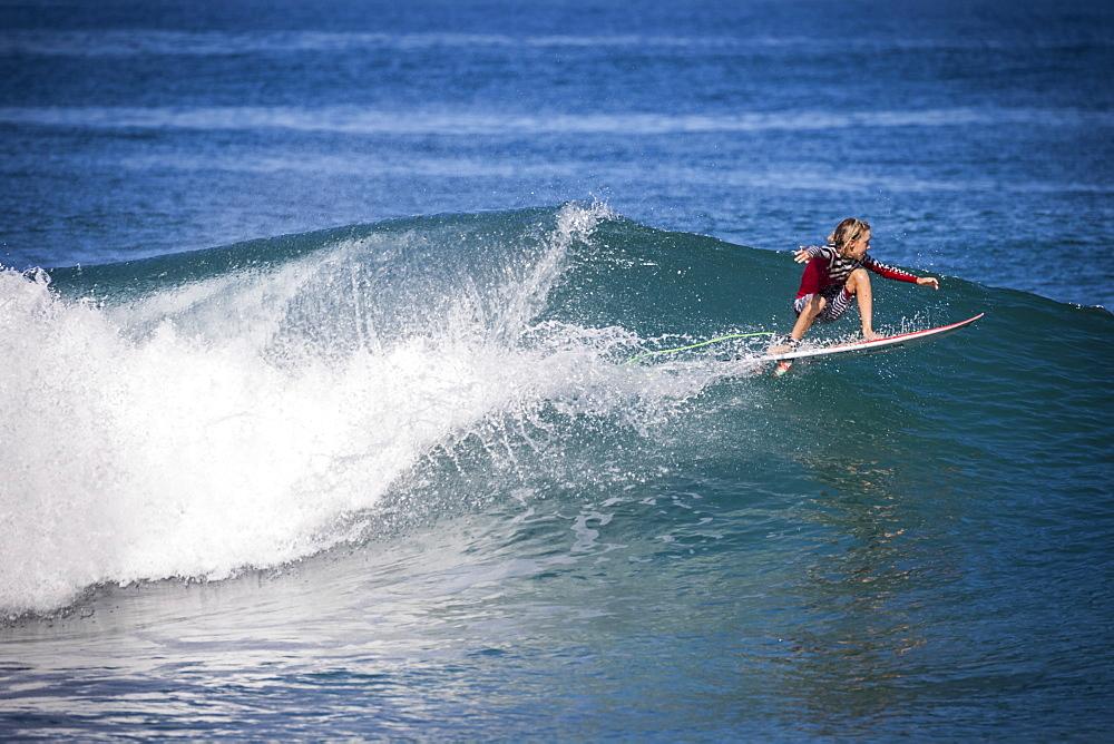 Side view shot of single boy surfing in sea