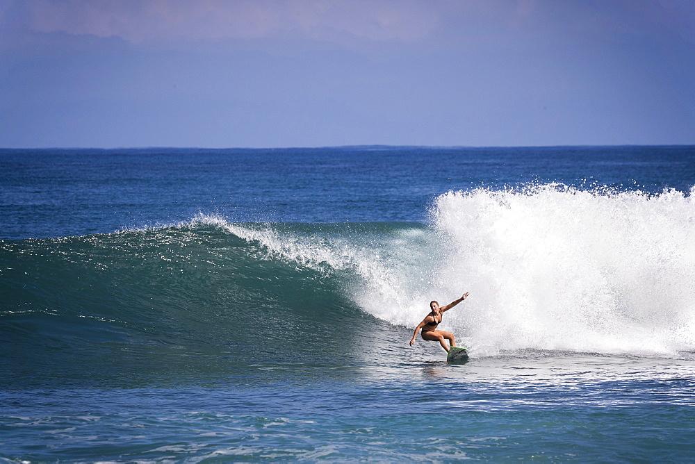 Distant view shot of single woman in bikini surfing in sea