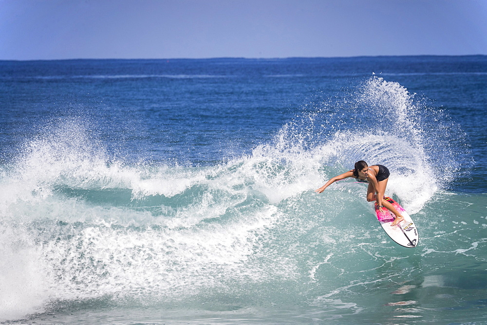 Full length shot of single woman surfing in sea