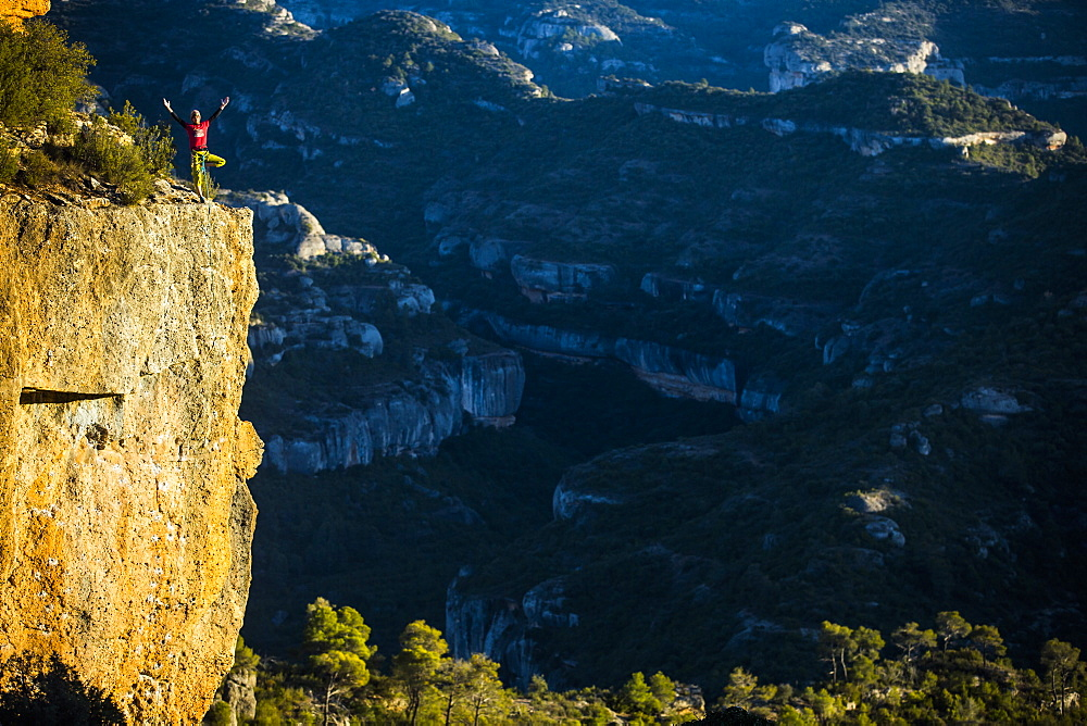 Distant view of single adventurous rock climber standing on edge of cliff after successful climb, Margalef, Catalonia, Spain