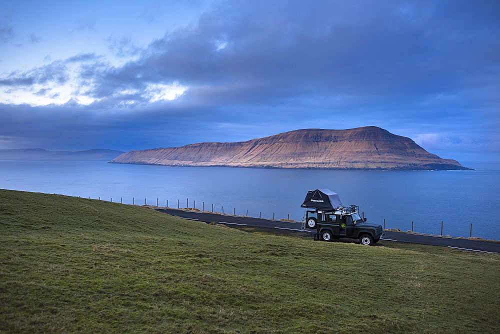 Side view of 4x4 car driving along coastline, Faroe Islands, Denmark