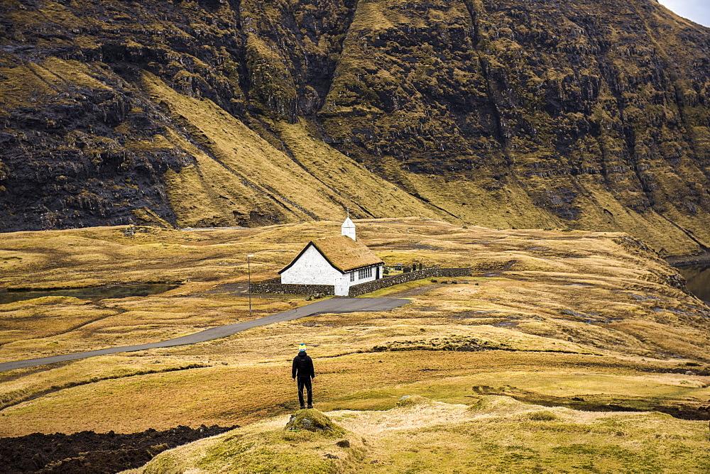 Rear view of man standing near sod roof house, Faroe Islands, Denmark