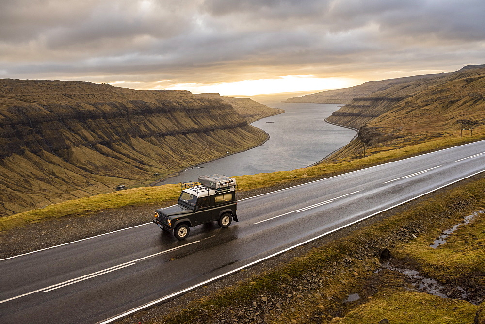 4x4 car driving along road on seashore, Faroe Islands, Denmark