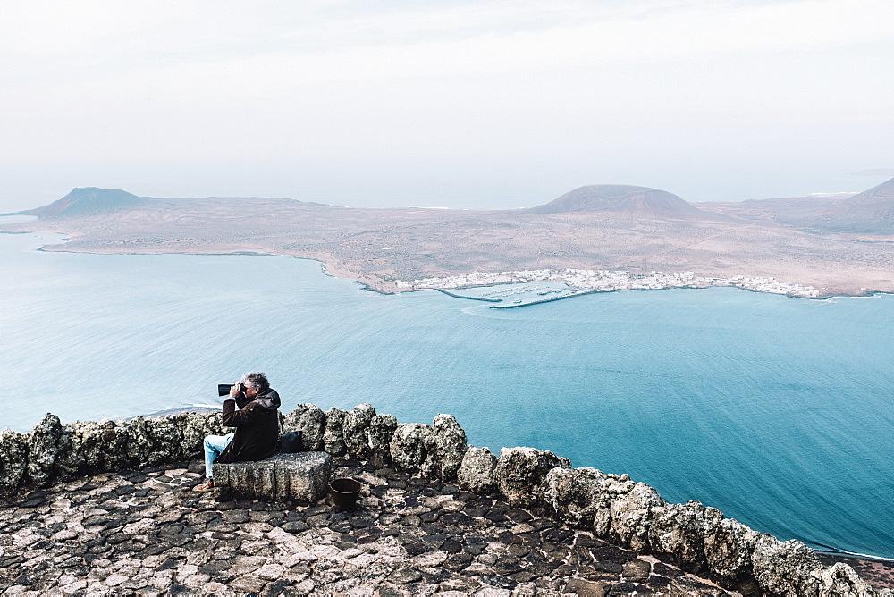 Man looking through binoculars at landscape with Isla de La Graciosa from viewpoint at Mirador del Rio, Lanzarote, Canary Islands, Spain