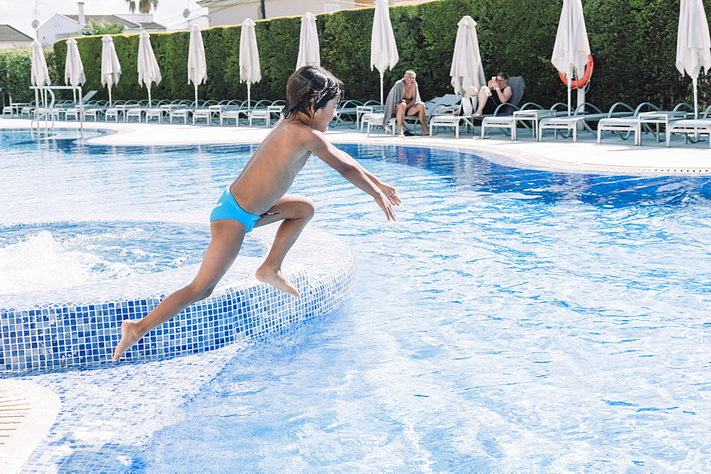A kid jumps in a hotel pool, Mallorca, Balearic Islands, Spain