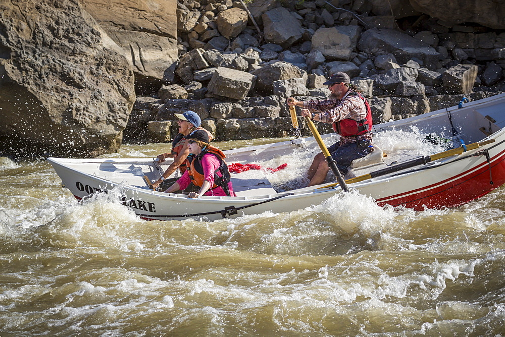 Man and two women sailing through rapids of Green River in Desolation Canyon, Utah, USA
